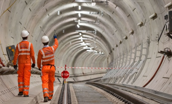 Two workers walk through a Crossrail tunnel in London